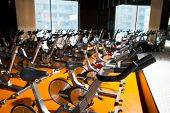 image of cardio exercise  - Aerobics spinning exercise bikes gym room with many in a row - JPG