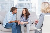 stock photo of psychological  - Couple looking to each other during therapy session while therapist watches - JPG