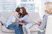 Couple reaching break through in therapy session sitting on the couch as therapist watches