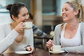 stock photo of canteen  - Two students having fun while sitting in college coffee shop and drinking coffee - JPG