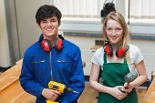 stock photo of hammer drill  - Two students standing in a woodwork class while holding a driller and a hammer - JPG