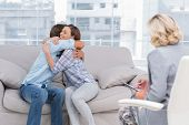 stock photo of couch  - Young couple cuddling on the couch while therapist watches - JPG