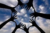 stock photo of racial diversity  - Conceptual peace and cultural diversity symbol of multiracial hands making a circle together on blue sky background - JPG