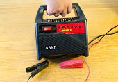 stock photo of accumulative  - Hand hold car automobile battery accumulator 6V 12V 6AMP charger - JPG