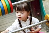 stock photo of playgroup  - Portrait of beautiful young girl on the playground - JPG