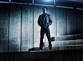 stock photo of rapper  - cool urban african american man on distopic concrete steps - JPG