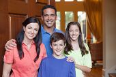 foto of entryway  - Hispanic father caucasian mother and mixed ethinicity son and daughter standing in entryway beside large wooden door of large home living room with tall windows in background - JPG