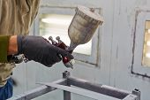 stock photo of air paint gun  - Male hand in glove with spray paint gun - JPG