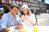 stock photo of churros  - Cheerful couple of tourists eating churros in Madrid - JPG