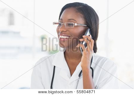 Smiling female doctor using mobile phone in the hospital