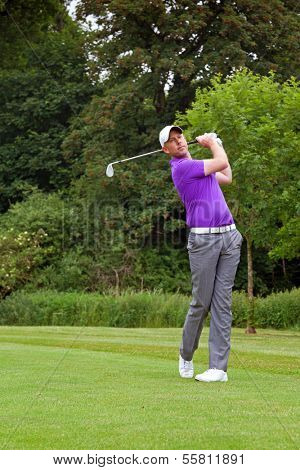 Photo of a golfer addressing the ball and playing a wedge shot into the green. Series of five in the set.