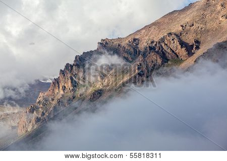 Mountain rocks covered by clouds