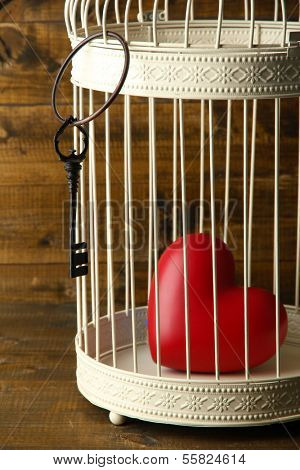 Heart in decorative cage  on wooden background