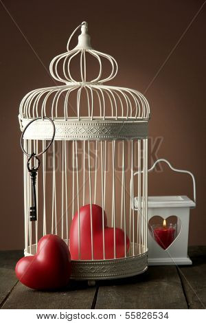 Hearts in decorative cage on wooden table, on brown background