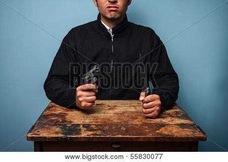 Thug At Table With Gun And Knife