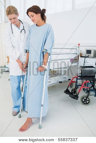 Full length of a doctor helping patient in crutches at the hospital