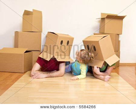Family Having Fun Unpacking In Their New Home