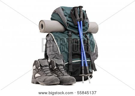 Hiking equipment, rucksack, boots, poles and slipping pad isolated on white background