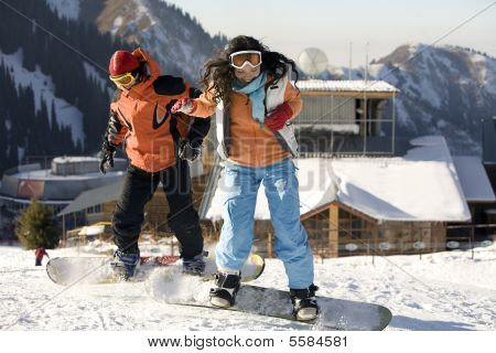 A Lifestyle Image Of Two Young Adult  Snowboarders