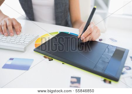 Close-up mid section of a female photo editor using graphics tablet in a bright office
