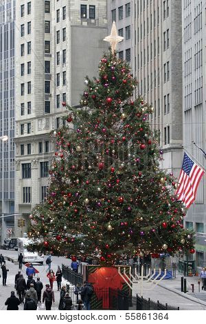 NEW YORK - DEC 19: Pedestrians walk past a Christmas tree near the New York Stock Exchange on Dec  19, 2013 in New York City.