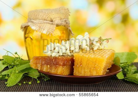 Jar of honey with flowers of lime, acacia on color bamboo mat on bright background