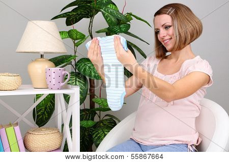 Young pregnant woman sitting on armchair and folding baby wear at home
