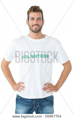 Portrait of a happy male volunteer standing with hands on hips over white background