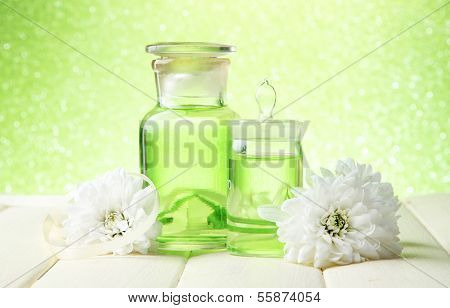 Glass bottles with color essence, on wooden table, on green background