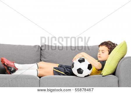 Boy in sportswear with a football sleeping on a modern sofa isolated on white background