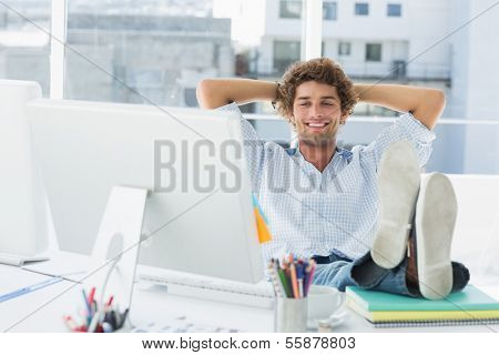 Relaxed casual young business man with legs on desk in a bright office