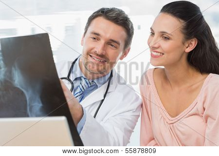 Male doctor explaining x-ray report to a smiling patient in medical office