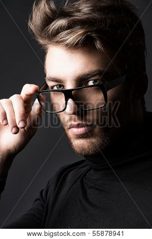 Portrait of an imposing man in elegant black clothes and glasses posing over dark background.