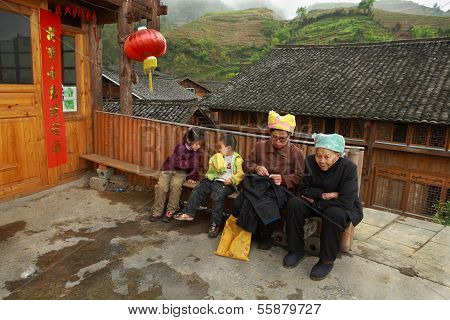 Rural China, Asian Grandmother With Grandchildren, Sit On Bench.