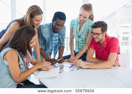Group of casual artists working on designs in the creative office