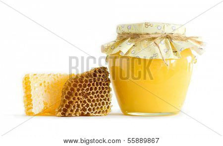 glass jar of honey and honeycombs on white background