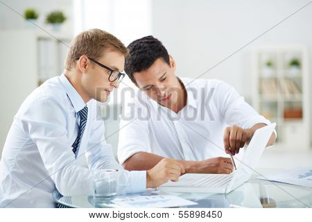 Portrait of smart businessmen discussing project in laptop at meeting