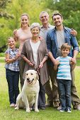 stock photo of extend  - Portrait of an extended family with their pet dog standing at the park - JPG