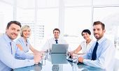 stock photo of half-dressed  - Smartly dressed young executives sitting around conference table in office - JPG