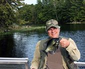 stock photo of crappie  - fisherman holding a crappie caught on a freshwater lake - JPG