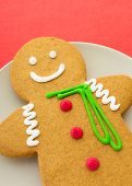 image of ginger man  - Gingerbread man on red background - JPG