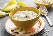 stock photo of porridge  - Porridge with bananas in a yellow bowl on the table - JPG