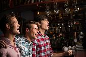 stock photo of indoor games  - Three men stand in a row embracing smile and look in front of you - JPG