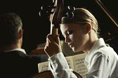image of cello  - Young beautiful woman playing cello in orchestra - JPG