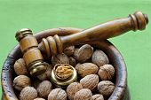 Closeup photo of Walnuts in a wooden bowl with a Nutcracker hammer