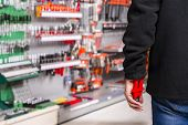 image of offensive  - male shoplifter stealing tools in a hardware store - JPG