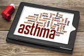 stock photo of asthma inhaler  - asthma word cloud on a digital tablet screen with an inhaler - JPG