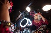 stock photo of cross-dressing  - Female impersonator adjusting hair in dressing room - JPG