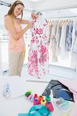 stock photo of dress-making  - Side view of a beautiful female fashion designer working on floral dress at the studio - JPG