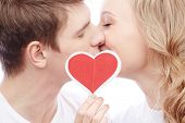 foto of amor  - Portrait of young amorous couple kissing while girl holding red paper heart - JPG